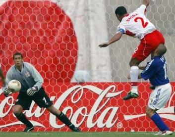 seorang pemain bola yang hendak menyundul bola yang sedang melambung ke atas dan ia meloncat sangat tinggi dan jatuh tepat diatas muka lawan