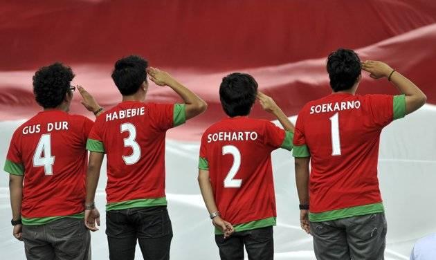 Empat suporter Indonesia dengan nama punggung Soekarno, Soeharto, Habiebie dan Gus Dur di kaosnya memberikan hormat kepada bendera merah putih. (ANTARA/Prasetyo Utomo)