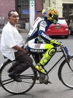 Valentino rossi beralih profesi menjadi tukang ojeg sepeda, klik WOW oke..