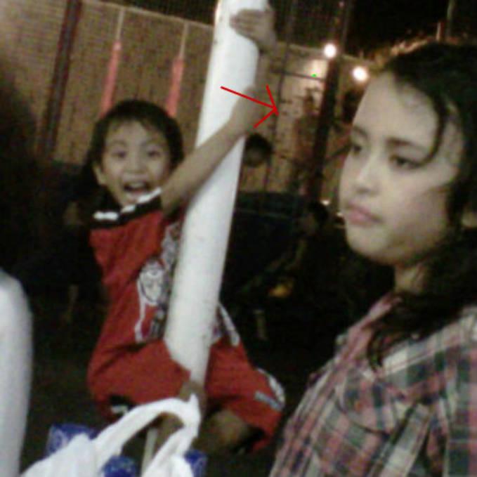 liAt tanda panah ini foto adik gue sendiri di taman lampion jogjakarta ada sebuah pocong yg gak sengaja ke foto sama ibu gue ini asli nyata please the wow
