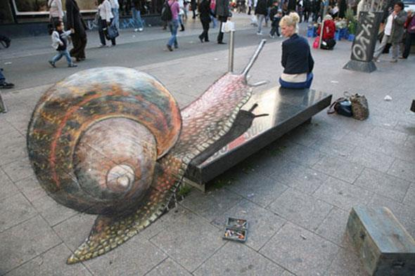 Seolah-olah wanita digambar ini bakal diserang sama siput ya! Tapi ternyata ini hanya lukisan, loh. Seorang 3D Pavement Artist berbakat, Julian Beever, menggunakan kapur untuk menggambar siput yang terlihat seperti Real 3D ini. Wow!