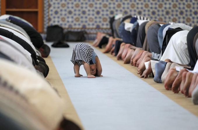 Anak kecil yang sedang menirukan orang sholat Dzuhur di Masjid Agung di Strasbourg Strasbourg, Prancis pada hari pertama Ramadhan, 9 Juli 2013...