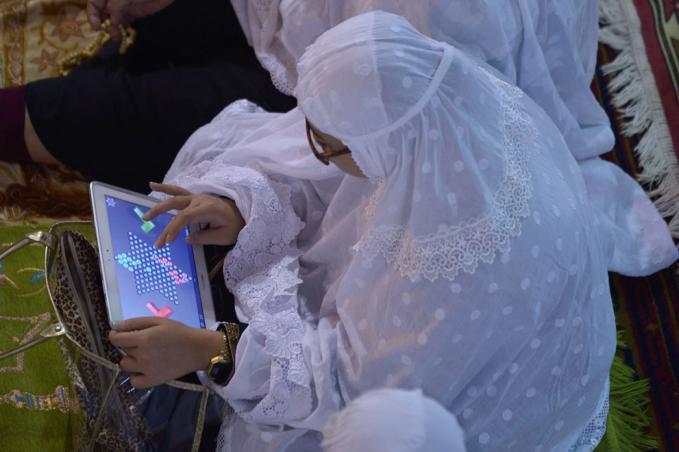 Seorang wanita Indonesia memainkan game pada tablet nya selama khotbah pada malam pertama Ramadan di masjid Istiqlal di Jakarta, pada tanggal 9 Juli 2013.