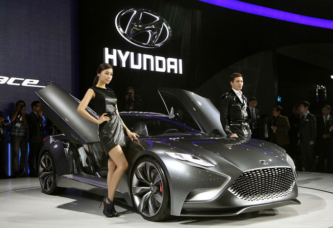 """South Korean models pose with a Hyundai Motors """"HND-9 Venace"""" during a press day of the Seoul Motor Show in Goyang, South Korea, Thursday, March 28, 2013. The exhibition, with 384 companies from 14 countries to participate."""