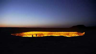 """Dua orang mengintip ke dalam kawah gas yang dikenal sebagai """"Gerbang Neraka"""" di Gurun Karakum, Turkmenistan. Api terus berkobar sejak para ilmuwan Soviet mulai menyalakannya pada 1971."""