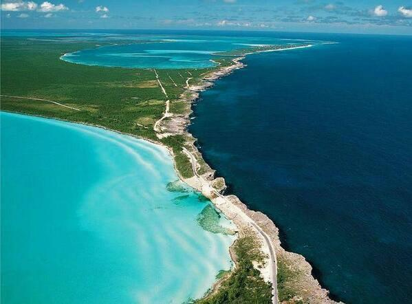 The Glass Window Bridge separates the light blue waters of the Atlantic Ocean and the turquoise-green Exuma Sound.