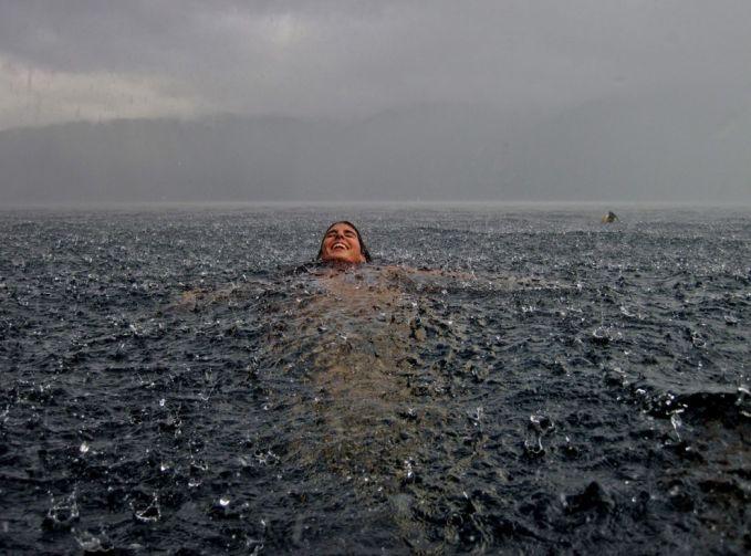 Seorang wanita yang berenang di danau di Chile saat hujan mulai turun