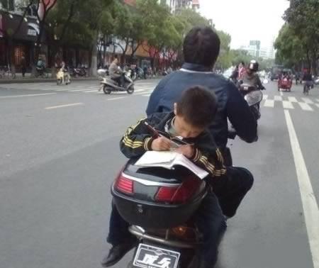 Demi mengerjakan tugas, anak ini rela mengerjakannya di atas sepeda motor