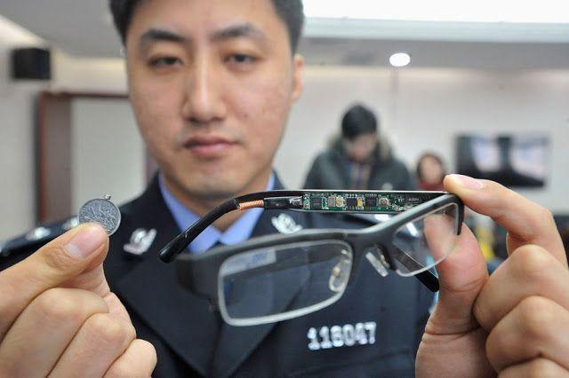 Seorang polisi menunjukkan kacamata canggih yang diselipi kamera tersembunyi serta sekeping koin yang berfungsi sebagai receiver.