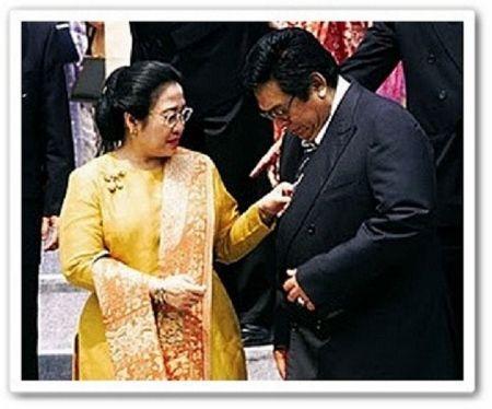 Menyempatkan diri buat benerin dasi suaminya, Pak Taufik Kiemas, di sela sebuah acara. Romantis juga, hihi