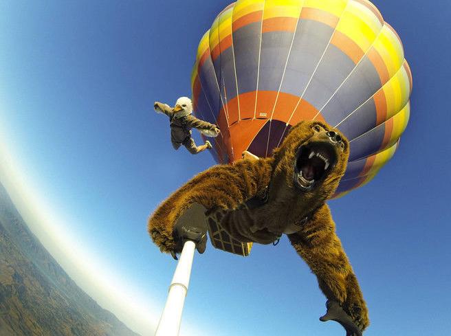 Atlet Mike Escamilla dan Travis Fienhage mengisi Halloween dengan berbeda. Melompat dari balon udara dengan kostum binatang mengerikan dan selfie saat mau mendarat.