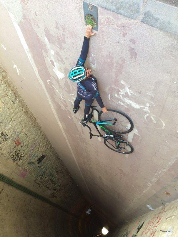 #1 Foto ini terlihat bahwa ada seorang pengendara sepeda yang bergantungan sambil memegang sepeda. Namun sebenarnya hanya tidur di lantai.