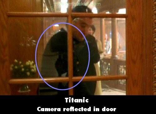 Kameranya kelihatan lewat pantulan kaca pintu tuh