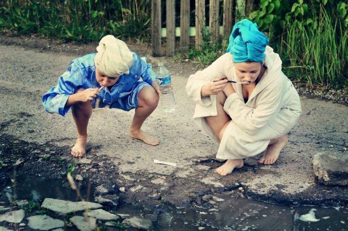 Lagi, terlihat dalam foto ini dua wanita sedang menyikat gigi dan mengambil air dari kubangan di jalan.