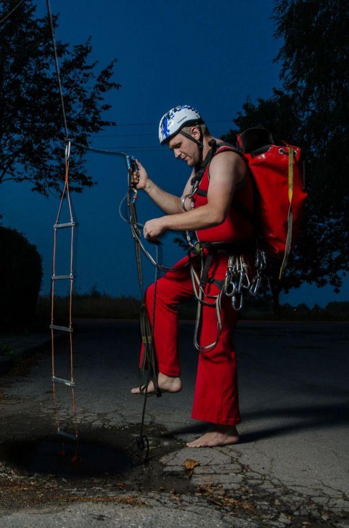 Foto ini mengandaikan seseorang akan terjun dengan tangga tali ke dalam kubangan.