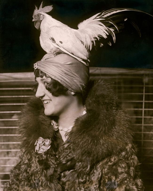 Seorang gadis pada tahun 1926 berfoto memakai topi yang diatasnya berisi ayam jantan. Kok nggak takut kabur ya ayamnya..hehe