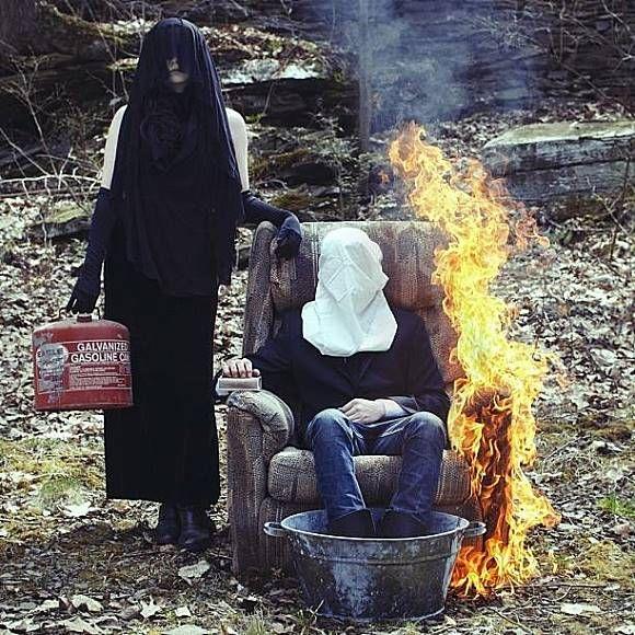 Foto ini begitu sangat misterius. Seorang perempuan berkerudung yang menutupi wajahnya sedang membawa gas ditangannya. Disebelahnya ada seorang pria dengan penutup kepala kain putih sedang duduk disofa terbakar..hii