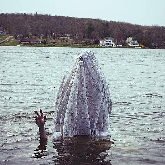 Pada gambar ini seperti orang yang tenggelam disebuah danau tapi diatasnya ada sosok meisterius berkain putih.