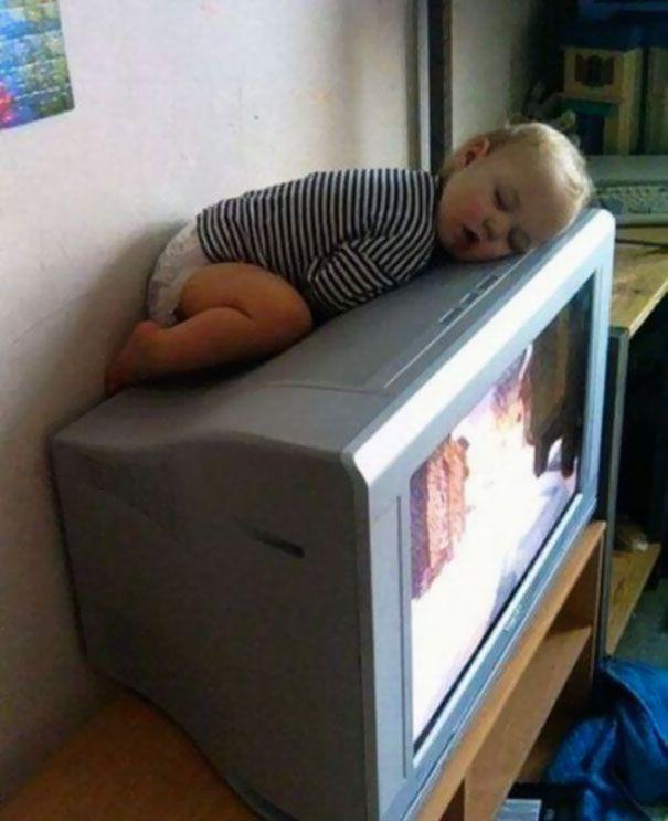Tidur di atas TV. Karna tidur di atas TV lebih hangat daripada tidur di kamar.