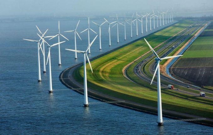Potret tanggul modern, kincir angin dan jalan raya yang bersih di Belanda yang dilewati berbagai macam kendaraan. Bersih banget ya tempatnya.