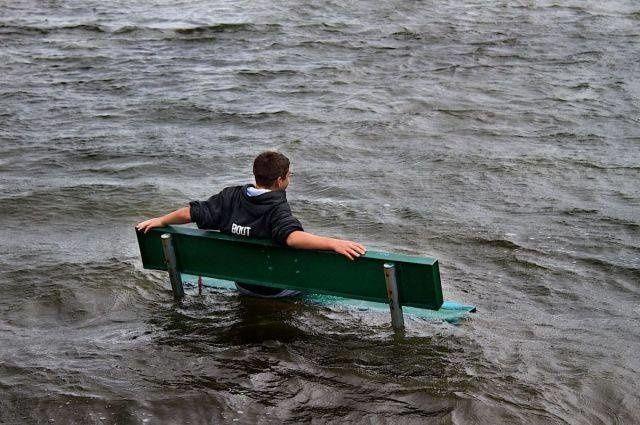 Udah tahu lagi banjir, tapi pemuda ini malah duduk bersantai dikursi yang digenangi air. Semoga aja nggak tenggelam deh..