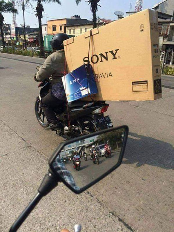 Beli TV segede gaban sekaligus dengan PSnya, orang Indonesia ini lebih memilih membawanya menggunakan motor dibandingkan harus sewa mobil untuk mengantarnya kerumah.