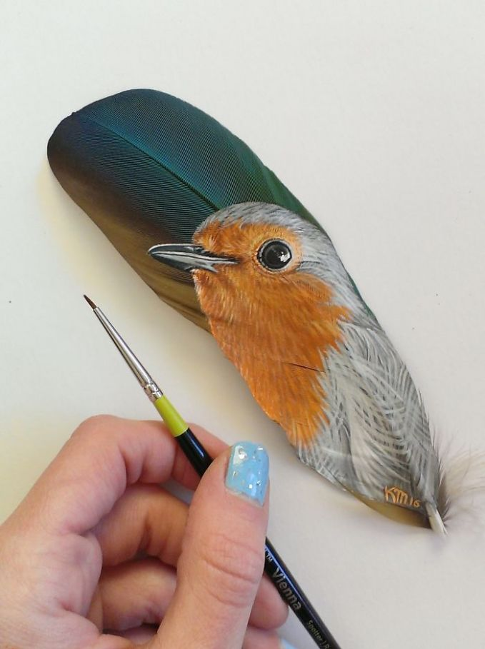 Burung Robin Eropa dilukis di bulu burung Macaw yang berwarna biru keemasan.