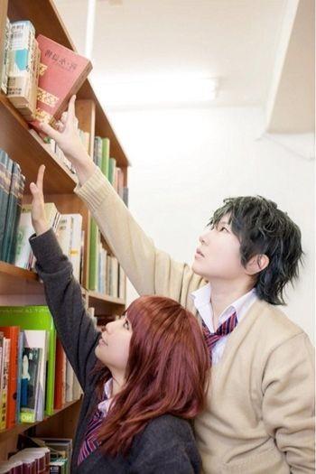 Terlihat seorang laki-laki sedang menolong perempuan yang kesusahan mengambil buku yang letaknya terlalu tinggi.