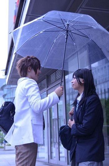 Terlihat seorang pria sedang meyodorkan payung pada wanita yang ada didepannya.