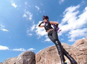 Seorang Cosplayer cantik sedang berfoto dengan latar belakang tebing batu yang tinggi.