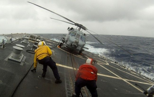 Gambar tersebut adalah para pekerja di kapal induk yang bertugas mengecek kekencangan tali pengait pada kapal ataupun pesawat yang dibawa pada saat badai berlangsung.