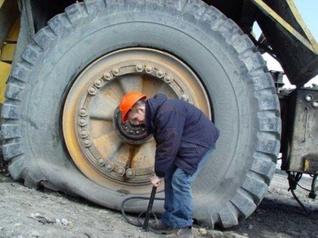 Hahaha... Yang satu ini cukup menggelikan. Pekerja tambang yang sedang memompa dan menambal ban kendaraan besar. Mana mompanya pake pompa sepeda dayung pula...