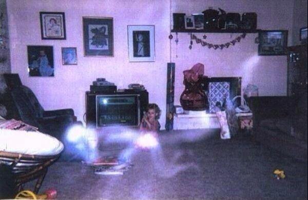 Dalam foto ini terlihat anak balita sedang berfoto di ruang keluarga. Anehnya, didepan gadis kecil itu ada sesosok bayangan putih yang melintas seperti sedang merangkak. Kira-kira apa ya Pulsker?