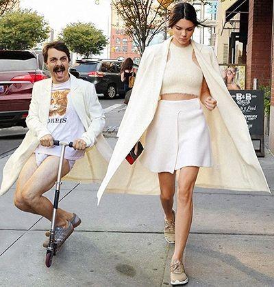 Foto ini ceritanya diambil secara candid saat Kendall Jenner berjalan di terotoar kota. Tapi ada pria yang menggunakan mantel dan hanya mengenakan celana dalam sedang bermain otopet. Merusak foto banget deh!