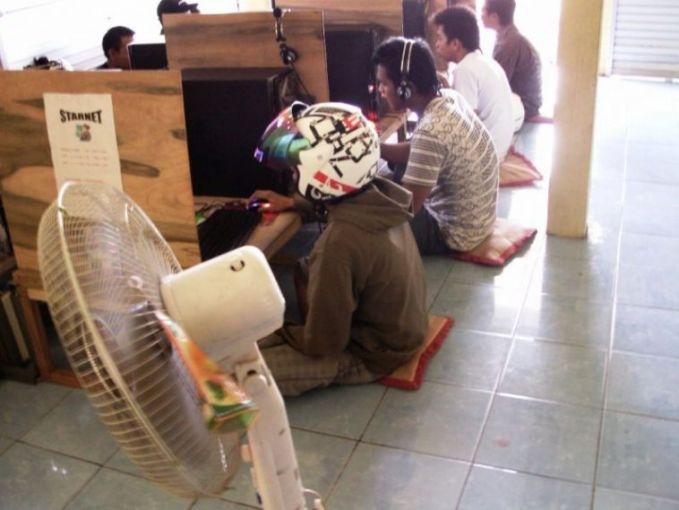 Di warnet Yang lainnya main game pakai earphone, pemuda ini malah antimainstream banget, main game online pakai helm. Ada yang tahu maksudnya nggak Pulsker?
