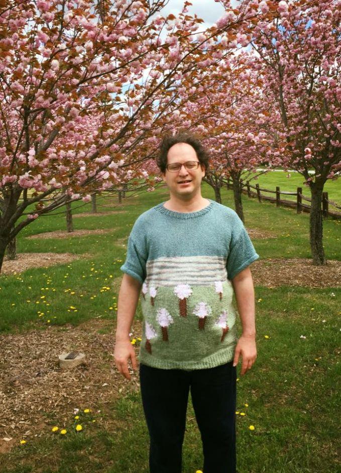 Foto ditengah-tengah pohon sakura dengan sweater yang bertemakan sama pohon sakura.