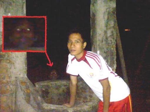 Sebenarnya nggak ada kerjaan juga sih kenapa pria ini foto dengan latar belakang sumur saat malam hari. Karena sumur juga diyakini menjadi tempat favorit atau tempat tinggal hantu. Hasilnya? lihat kotak merah pada gambar dibawah ini, ada penampakkan kepala dengan mata yang menyala.