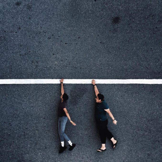 Dua orang sedang bergelantungan diatas tali berwarna putih. Padahal sebenarnya mereka hanya berfoto dengan merebahkan tubunya dijalan yang ada markanya.