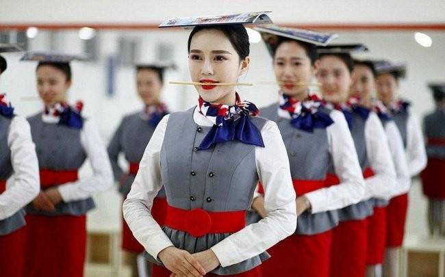 Mengigit sumpit melatih agar selalu tetap tersenyum, dan harus menyeimbangkan majalah yang ada diatas kepalanya.