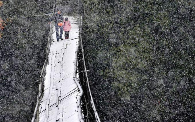 Ditengah salju yang turun dan angin yang berhembus nampak salah satu orang tua bersama anaknya mengantar ke sekolah melewati jembatan yang rusak. Foto ini diambil di wilayah Dujiangyan, propinsi Sichuan, Cina.