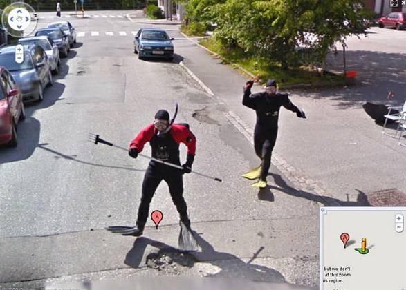 Diving dipinggir jalan Pada gambar ini terlihat dua orang dewasa sedang menggunakan kostum menyelam di tengah jalan. Dan sepertinya tingkah laku mereka juga seperti sedang berenang. Mau ngapain ya?