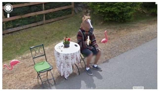 Tuan Kuda Setelah topeng burung, kali ini adalah topeng kuda. Pada foto ini terlihat seorang pria menggunakan topeng sedang duduk dipinggir jalan. Selain itu terdapat juga satu kursi kosong dan bunga di atas meja. Ia juga memegang sebuah pisang yang telah dibuka.