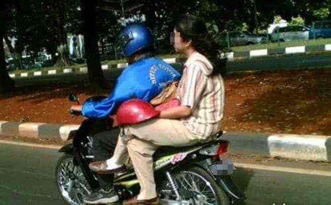 Aduh, si ibu ini tanpa penuh dosa dan dengan duduk santai helmnya cuma dipakai di dengkul gitu pulsker.