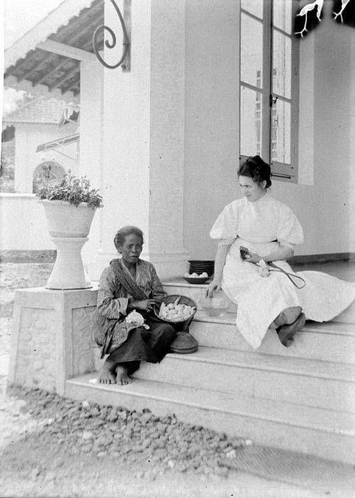 Foto pertama adalah seorang nenek penjual telur yang sedang menawarkan dagangannya pada noni Belanda didepan rumahnya.