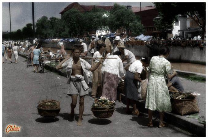 Ini adalah sebuah potret pasar tradisional jaman dulu, terlihat hiruk pikuk pasar dan seorang bapak yang memikul dagangannya.