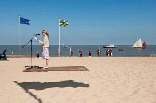 Foto cewek yang lagi ngasih sambutan di pinggir pantai ini seolah dia lagi naik karpet terbang. Padahal dia lagi berdiri di atas sebuah papan. Disebelahnya ada bendera berkibar dan bayangannya pas banget disampingnya.