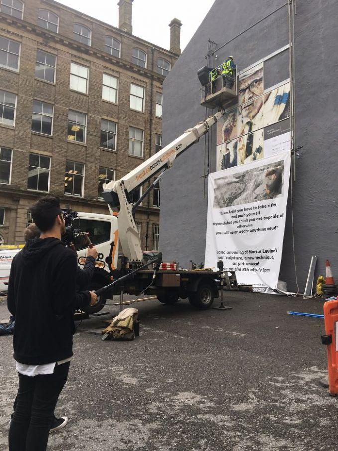 Seperti ini proses pembuatannya. Sang seniman dibantu beberapa rekannya harus naik turun kayak gitu buat memasang dan memaku tembok untuk media seninya. Dan lukisan tersebut terdiri dari 12 bagian.