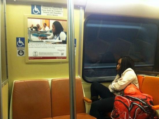 Seorang wanita yang duduk di dalam KRL ini terlihat sama persis dengan foto wanita yang ada pada iklan di atasnya.
