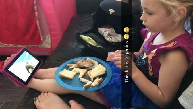 Begitu pula halnya degan gadis cilik ini Pulsker. Dengan santainya dia memanfaatkan kedua kaki untuk dudukan gadget untuk nonton sembari makan roti.