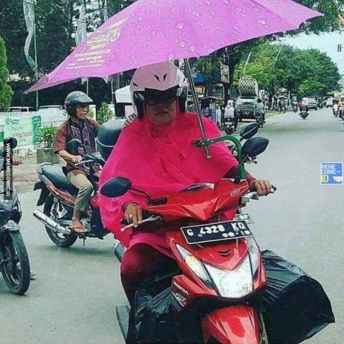 Daripada kehujanan, mending pakai payung aja pakai sepeda motor.